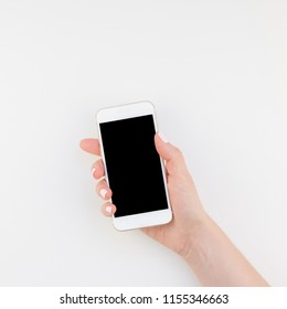 Woman hand with pastel manicure polish holding smartphone isolated on white background with copy space in minimalism style. Square Template mock up for feminine blog social technological media