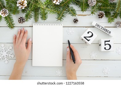 Woman hand with pen and blank notebook. Christmas decoration Fir tree, Pine cones and perpetual calendar 25 december on white background Flat lay frame mockup. Minimal design