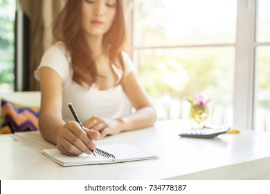 Woman hand with pen writing some idea on small notepad while sitting on chair in house.