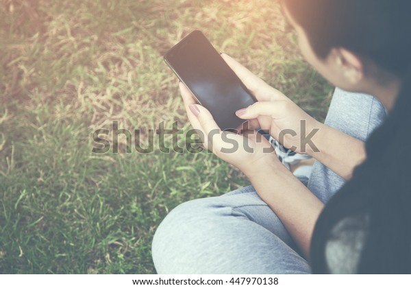 Woman hand phone over green grass