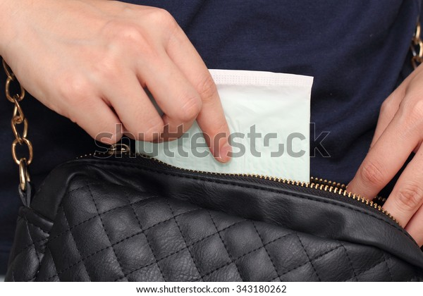 woman hand picking up sanitary napkin from her hand bag