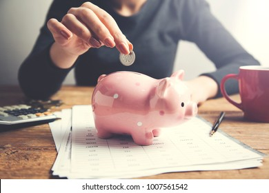 woman hand piggy bank and coins on table