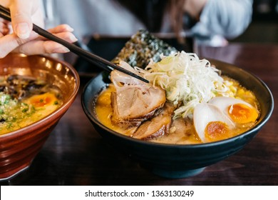 Woman hand pinching noodle in Ramen Pork Bone Soup (Tonkotsu Ramen) with Chashu Pork, Scallion, Sprout, Corn, Dried Seaweed and boiled egg served in black bowl.