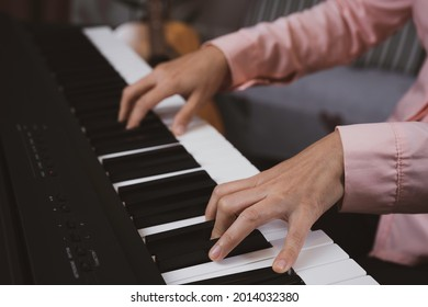 Woman hand in pink shirt pressed paino key, woman playing paino, practiceing, relaxing, teaching concept.