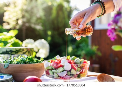 Woman hand pouring flavored olive oil to fresh vegetable salad. Preparation healthy vegetarian food for garden party outdoors