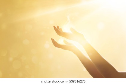 Woman hand praying for blessing from god on sunset background