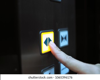 Woman hand press open button  to extend door inside elevator.