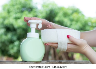 Woman hand press pure green plastic pump bottle on Loofah and take cleaner foam,Putting whip foam soap bottle with foam on loofah,spa pedicure treatment,Spa decoration,towel and Frangipani flowers,