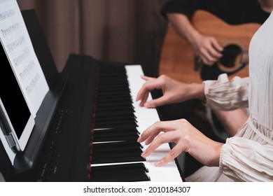 A woman hand pressed on paino keyboard while her friend playing guitar, playing music together at home, tablet and key note paper on paino holder. Relaxing time, practicing, learning music.