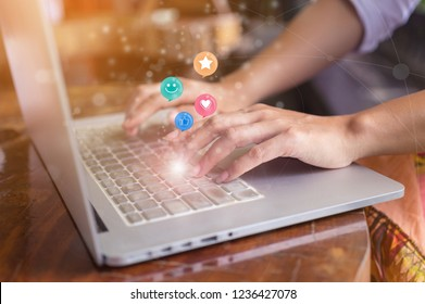Woman hand pressing on laptop computer with smiley face, like, love and star emoticon on virtual screen, Customer service evaluation concept.