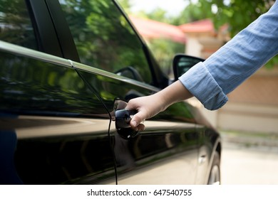Woman hand pulling car door handle to open the a car outdoors