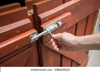 Woman hand pulling latch lock of the brown wooden fence for safety.