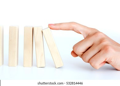 Woman hand pushing a wooden block to start a domino effect