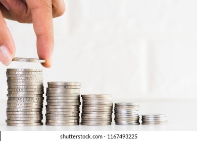 Woman hand put a coin on stacking coins on white brick block background. Money saving concept.