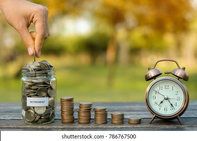 Woman hand putting coin, full of coins stack, glass jar and retro alarm clock on wooden table in the morning sunlight. business, investment, retirement, finance and Money Saving for the future concept