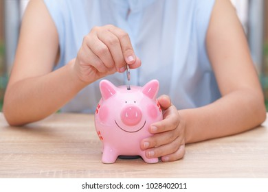 woman hand putting a coin into a pink piggy bank on wooden desk - save money concept.