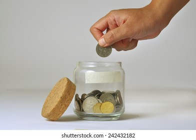 Woman Hand Putting a Coin into Glass Bottle
