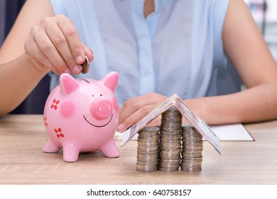 Woman hand putting a coin into a pink piggy bank on wooden desk - save money to buy house concept