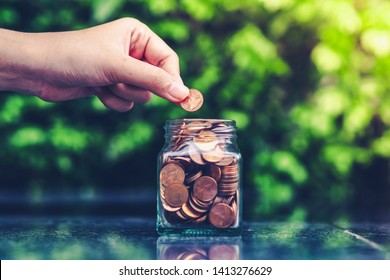 Woman hand putting coins in jar glass. Saving Money for prepare in the future. Saving money concept.