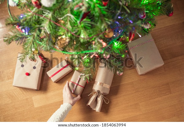 Woman hand putting hand made gift wrapping in a kraft paper under christmas tree. Presents for family. Top view. Flat lay.