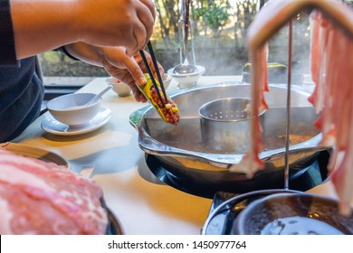 Woman hand putting meat ball into the hotpot