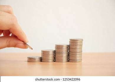 Woman hand putting money coin stack growing business and saving money for future.