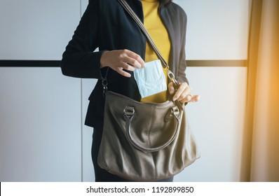 Woman hand putting sanitary napkin in handbag,White menstrual pad,Menses