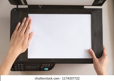 woman hand putting a sheet of paper into a copying device