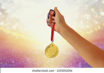 woman hand raised, holding gold medal against glitter background. award and victory concept