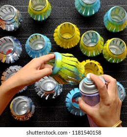 Woman hand recycling cans of beer by cut and spray paint to make lantern for mid autumn festival
