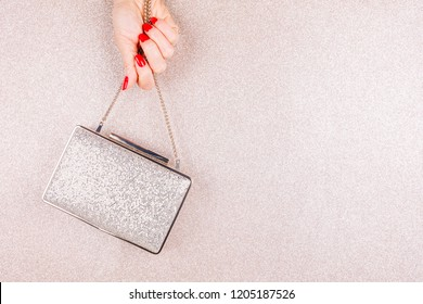 Woman hand with red manicure holding a small golden evening clutch. Holiday, party and celebration concept. Horizontal