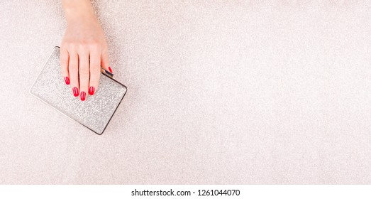 Woman hand with red manicure holding a small golden evening clutch. Holiday, party and celebration concept. Horizontal, wide screen banner format
