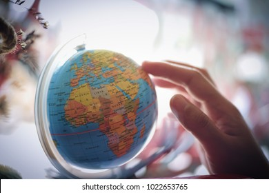 Woman hand select destination on the world map globe ball, Travel concept. vintage color. selective focus.