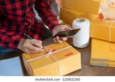 woman hand selling online from home packing parcel for order another hand holding smart phone