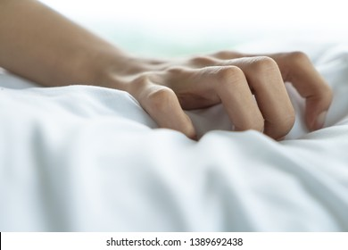 Woman hand with sex orgasm on white bed. Couple lover marriage activity lifestyle pleasure intimacy moment.Hand sign orgasm girl enjoying sensual, making love, having sex passion in bed room.
