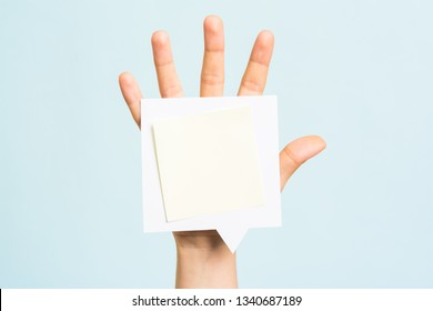 Woman hand showing a blank empty note or negative space for text on speech bubble over hand and blue background