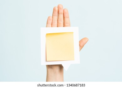 Woman hand showing a blank yellow sticky note with negative space for text on speech bubble over hand and blue background