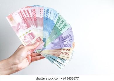 Woman Hand showing Indonesian Money Rupiah