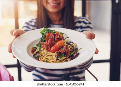 Woman hand showing spaghetti in the dish on the wooden table at restaurant