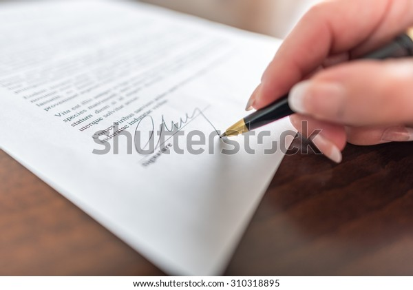 Woman hand signing a contract