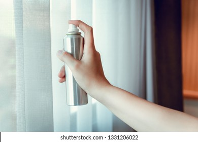 Woman Hand is Spraying Air Freshener to Curtains Window in Bedroom, Unpleasant smell and Aromatherapy Concept.