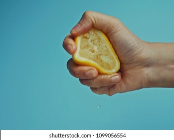 Woman hand squeezing a lemon half on pastel blue background. Food and drink ingredients preparing or bakery processing concept. (close up, selective focus, copy space)