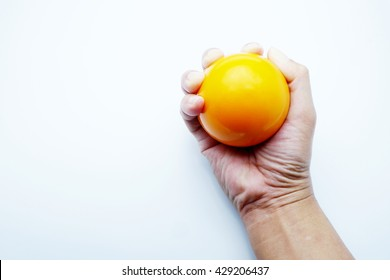Woman hand squeezing a stress ball with yellow color on white - gray background.