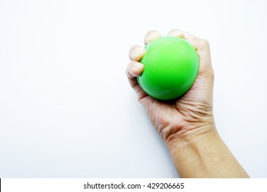 Woman hand squeezing a stress ball with green color on white - gray background.