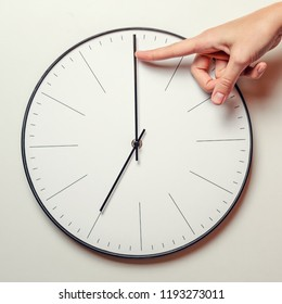 Woman hand stop time on round clock, female finger takes the minute arrow of the clock back, time management and deadline concept