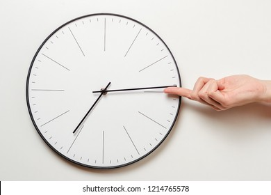Woman hand stop time on round clock, female finger takes minute arrow of the clock back, time management and deadline concept