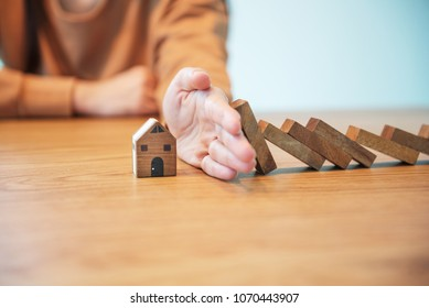 Woman hand stopping risk the wooden blocks from falling on house, Home insurance and security concept.
