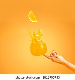 Woman hand support fly glass of orange drink with splash, juice slice orange falling in glass. Summer art food concept on orange background
