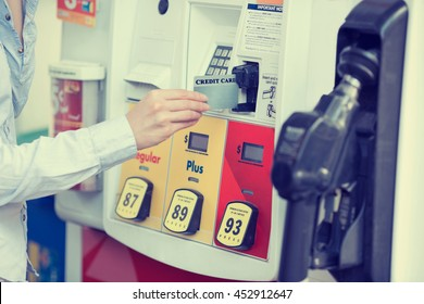 Woman hand swiping credit card at gas pump station.