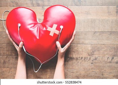 woman hand take care of red broken heart with bandage listening music on mobile phone, Broken heart concept on wood floor
